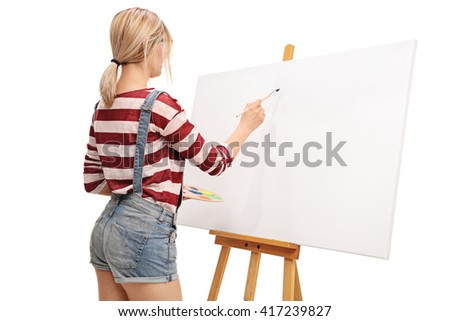 Rear view of a young female artist preparing to start painting isolated on white background - stock photo