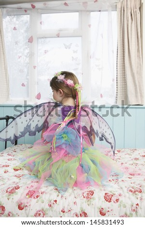 Rear view of a young girl in fairy costume sitting on bed looking through window - stock photo