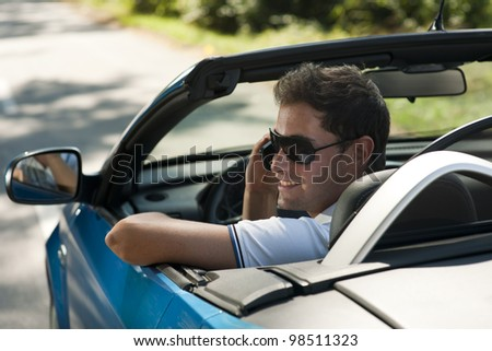 Rear view of a young man driving his convertible car - stock photo