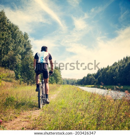 Rear View of a Young Man Riding a Bicycle on Nature Background. Healthy Lifestyle Concept. Copy Space. Instagram Styled Toned Photo. - stock photo