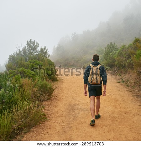 Rear view of a young man walking away from the camera on a dirt path nature trail with the natural surrounds disappearing into morning mist - stock photo