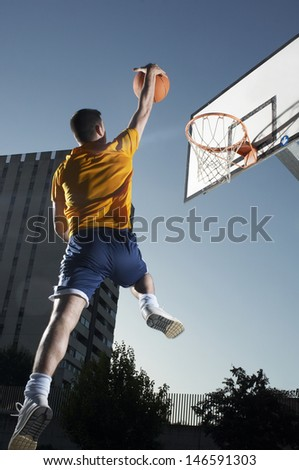 Rear view of a young man with basketball jumping towards hoop - stock photo