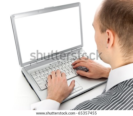 Rear view of a young man working of a laptop - stock photo