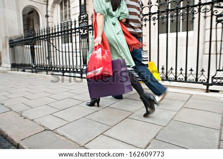 Rear view of a young tourist couple on holiday walking down an exclusive shopping street in London with classic stone buildings and holding carrier paper bags, outdoors. - stock photo