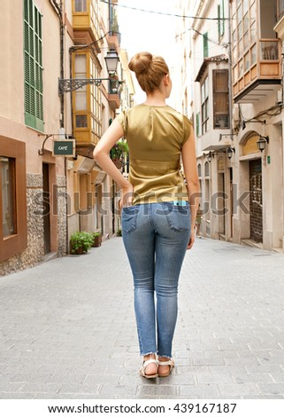 Rear view of a young tourist woman standing in a picturesque city destination street, sightseeing, enjoying a weekend holiday trip, with smart phone in pocket, sunny outdoors. Travel lifestyle. - stock photo