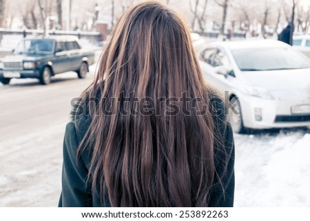 Rear view of a young woman covered with her long blond hair and looking at the street with cars. - stock photo