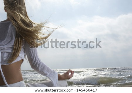 Rear view of a young woman meditating on beach facing the ocean - stock photo