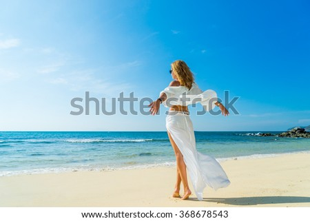 Rear view of a young woman on the sand near the indian  ocean - stock photo