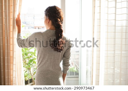 Rear view of a young woman wearing a robe and holding the curtains open to look out of a large light window at home, interior. Positive and aspirational lifestyle. Woman looking out a window, indoors. - stock photo
