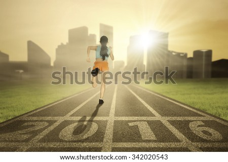 Rear view of a young woman wearing sportswear start to run at field with numbers 2016 - stock photo