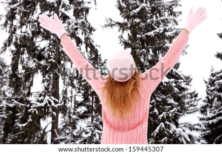 Rear view of a young woman with blond hair and a pink jumper, hat and gloves with her arms raised up in the air, enjoying the snow trees in the winter mountains, outdoors. - stock photo