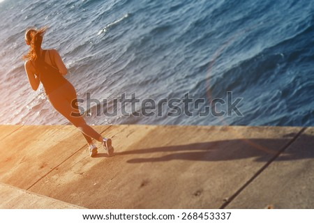 Rear view of a young woman with fitness body running at the coastline next to the ocean, athletic girl jogging over amazing big waves background at sunny day - stock photo
