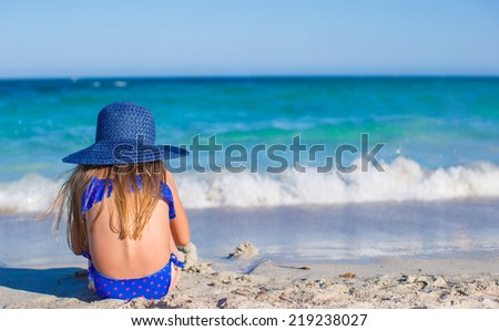 Rear view of adorable little girl in big blue straw hat at white beach - stock photo