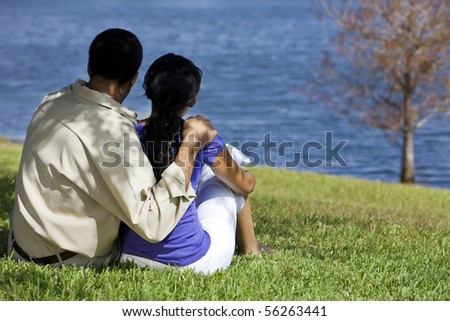 Rear view of African American man and woman couple sitting by a blue lake with a single tree. Concept shot for love, romance or loss. - stock photo