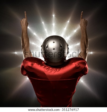 Rear view of American football player with arms raised against spotlight - stock photo