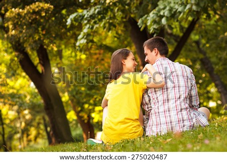 Rear view of an affectionate young couple sitting in park. - stock photo