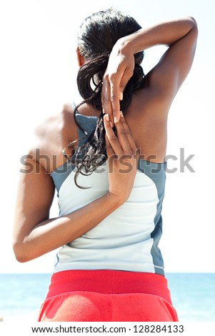 "Rear view of an ""african american"" woman stretching her arms behind her back while standing against a deep blue sky, exercising on a sunny day by the sea. - stock photo"