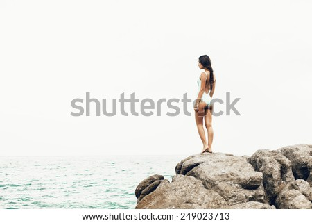 Rear view of an attractive african american black woman sitting and relaxing on a natural coastal rock high up, contemplating the sea against a blue sky. Well being healthy lifestyle. - stock photo