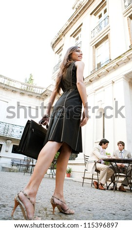 Rear view of an attractive elegant businesswoman walking to a business meeting in a luxury coffee shop terrace. - stock photo