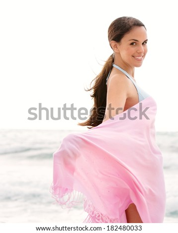 Rear view of an attractive young woman on holiday on a sunny beach turning to smile at camera while holding a floating pink fabric sarong around her body in the breeze. Travel lifestyle. - stock photo