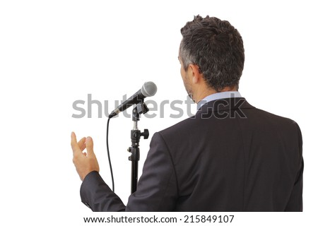 Rear view of an isolated male public speaker speaking at the microphone, pointing, symbol of leadership and international conferences - stock photo