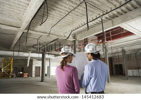 Rear view of architect and construction manager reading blueprint at site - stock photo