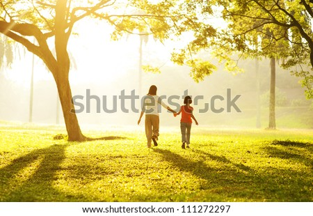 Rear view of Asian mother holding her daughter's hand running towards light - stock photo