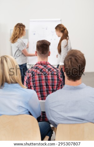 Rear View of Attentive Young Employees Listening to Female Supervisors Explaining Something About the Business Using Posters. - stock photo