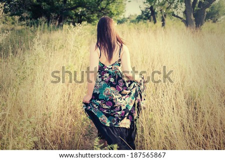 Rear view of beautiful brunette outdoors - stock photo