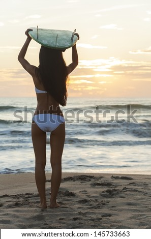 Rear view of beautiful sexy young woman surfer girl in bikini with white surfboard on her head on a beach at sunset or sunrise - stock photo