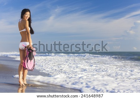 Rear view of beautiful young Asian Chinese woman in bikini with snorkel, mask & flippers on a deserted beach with blue sky - stock photo