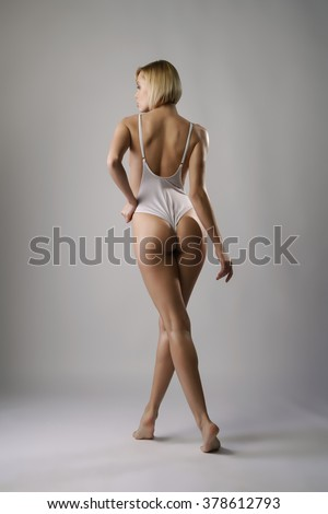 Rear view of blonde posing in sexy white bodysuit - stock photo