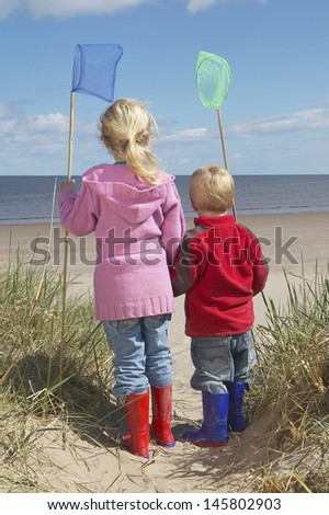 Rear view of brother and sister holding fishing nets on beach - stock photo