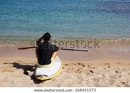 Rear view of brunette hair man sitting on the beach while enjoying good sunny day, male surfer waiting for the big waves sitting on beautiful shoreline,  - stock photo
