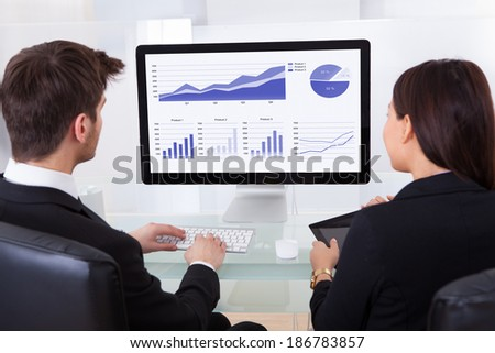 Rear view of business colleagues using computer at desk in office - stock photo