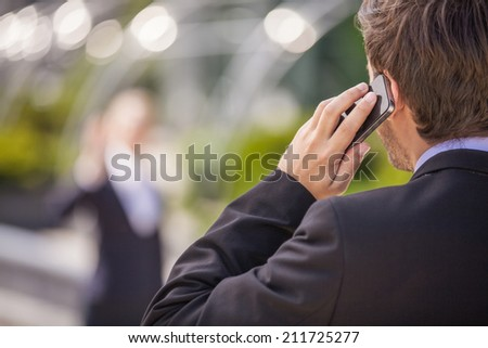Rear view of business man in black. young man talking on mobile phone  - stock photo