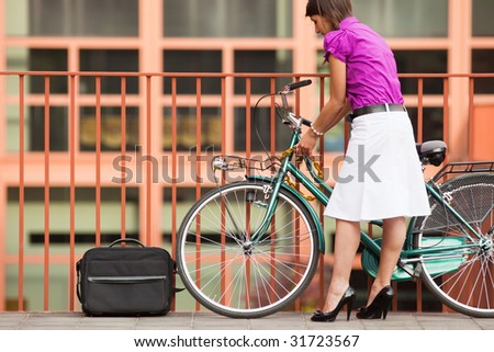 rear view of business woman locking padlock to her bike. Copy space - stock photo