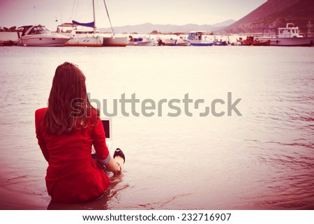 Rear view of business woman sitting at beach and working   - stock photo