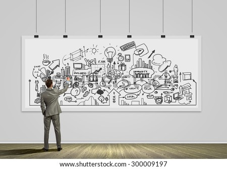 Rear view of businessman drawing business plan on white banner - stock photo