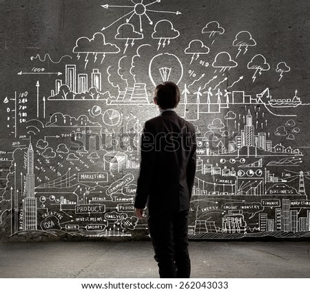 Rear view of businessman looking at chalk sketches on wall - stock photo