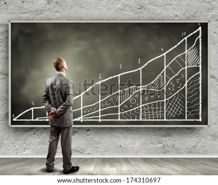 Rear view of businessman looking at chalkboard - stock photo