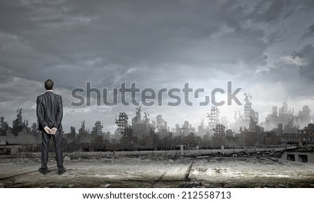 Rear view of businessman looking at ruins of city - stock photo