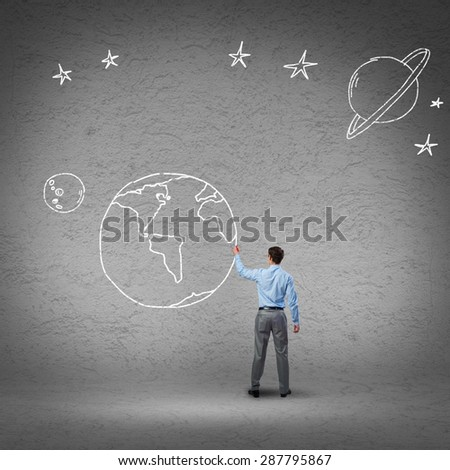Rear view of businessman presenting drawn Earth planet - stock photo