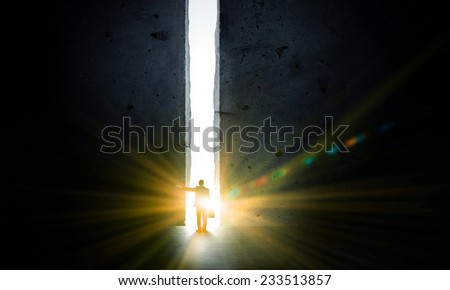 Rear view of businessman standing in light of way in wall - stock photo