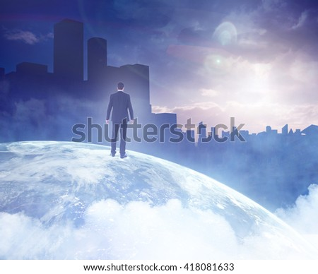 Rear view of businessman standing on a picture of the earth - stock photo