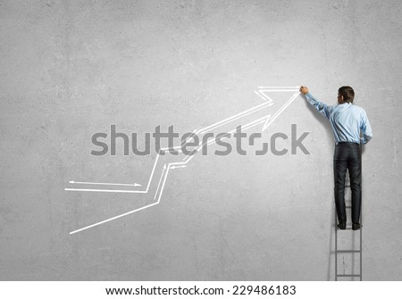Rear view of businessman standing on ladder and drawing graph - stock photo