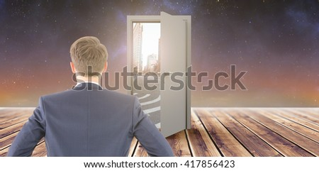 Rear view of businessman standing with hands on wiast against wooden planks - stock photo