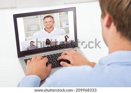 Rear view of businessman video conferencing on computer at desk in office - stock photo