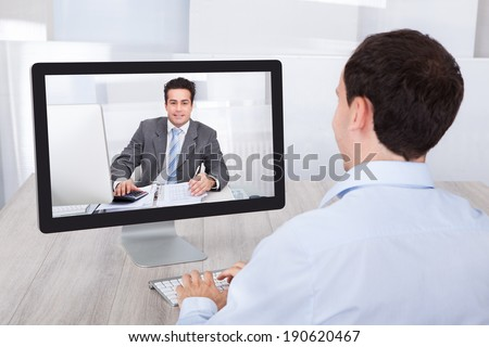 Rear view of businessman video conferencing with coworker on desktop PC at office desk - stock photo
