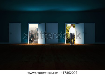 Rear view of businessman with hands in pockets against doors opening in dark room to show sky - stock photo